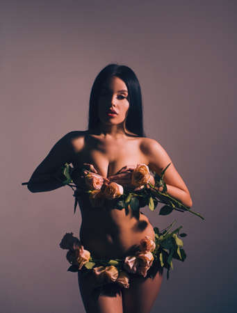 Young and sexy naked woman with rose flowers instead of underwear.