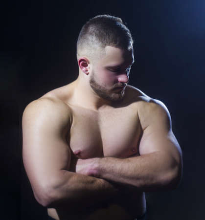 Strong athletic man, fitness model, torso, showing big muscles over black background. Stock Photo