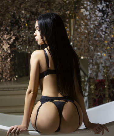 Sexy female booty in luxury bathroom in black lingerie.