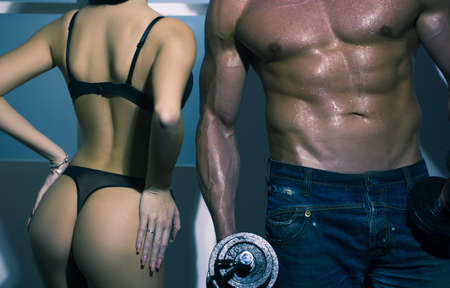 Bodybuilding, strong man and a woman posing near window.
