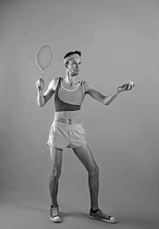 Funny playful young man tennis player with racket imitating ball serve. black and white. Stock Photo