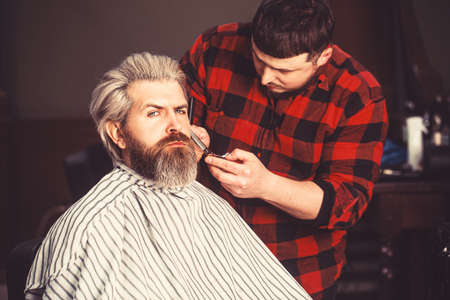 Cheerful caucasian man happy to be on the haircut with a professional hairdresser. Stock fotó