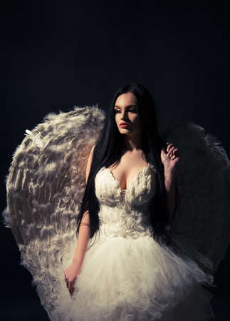 Woman angel with wings in heart shape. Fashion white dress.