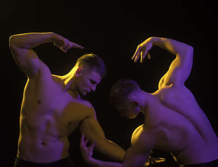 Twins muscular men in bodybuilder pose isolated on black background.