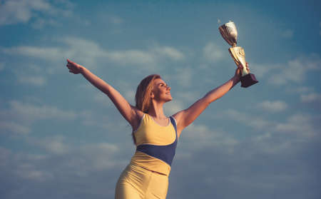 Young blonde sportswoman looking on champion Cup and posing with sky background. She is wearing yellow top and leggins. Standard-Bild