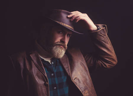 Cowboy in green shirt, leather Jacket and hat showing his small smile and touching his hat