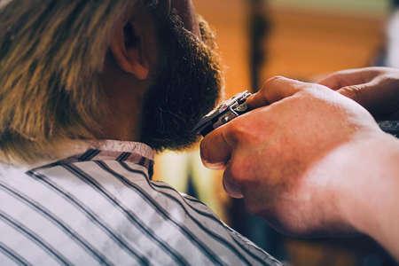 Beauty shop for men. Shaving a beard in a barbershop.