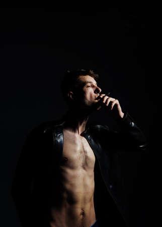 Smoking cigarette. Wearing black leather jacket. Studio shot against dark.