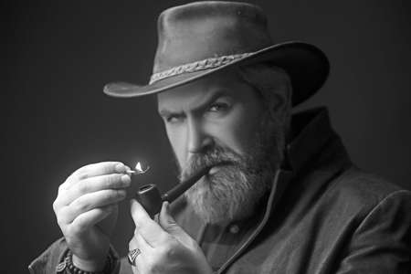 Bearded man smoking tradition pipe. Fashion portrait. Stock fotó