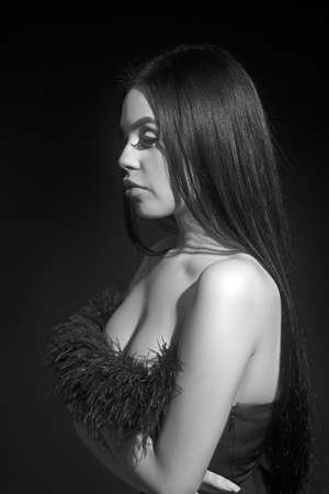 Attractive and sexy portrait of a long hair young woman in black dress in studio. Naked back. Fashion and glamour shot. Stock fotó
