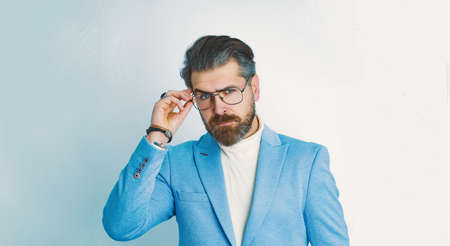 Portrait of serious fashionable handsome man in blue suit.