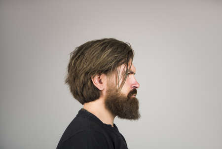 Side view portrait of bearded stylish young man looking away.
