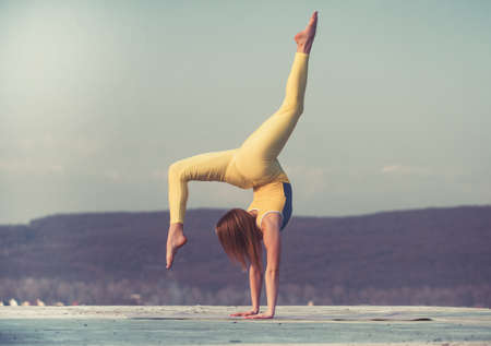 Beautiful athletic woman is stretching and makes a bridge on sky background. Foto de archivo