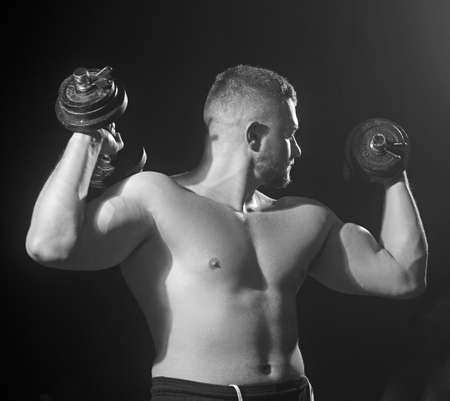 Muscular model young big man on dark background.