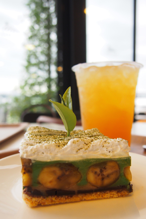 Green Tea Banoffee, a beautifully decorated bakery on a white plate and Lemon ice tea on the table in a bakery shop that overlooks the outside. Stock Photo