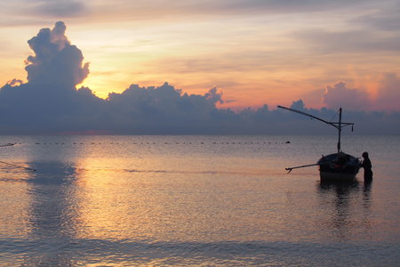 Sunrise, the colors of the morning sky, with the fishermen preparing the boat to go out to fish.