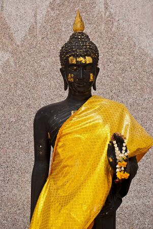 image of black Buddha covers a body with silk yellow gold cloth with marble wall and church shade