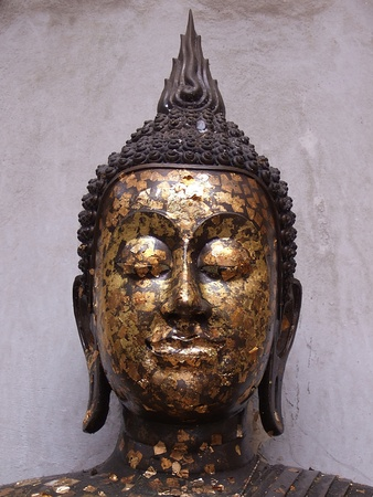 image of Buddha head  the art is like [ model ] Thai and the background  white old wall is ancient Stock Photo