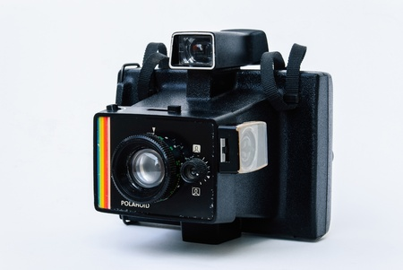 The old polaroid camera is black with white background Editorial