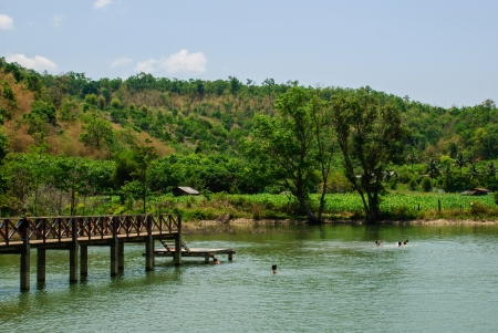 children is swimming in big swamp near the mountain