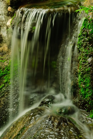 The small waterfall and the stone and the tourist attraction of Thailand Stock Photo