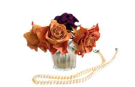 Composition of three dried roses and string of pearls                                photo
