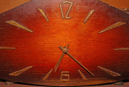 Old wooden clock with rusty arrows                               photo