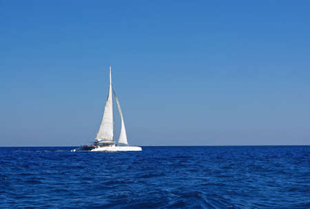 sailboat race: White boat with sails in the Mediterranean
