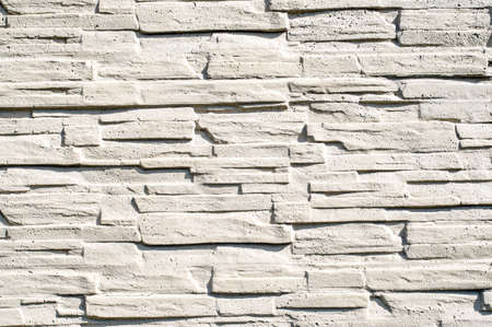 fastened: A fence made of narrow stones fastened by cement painted with white paint as background