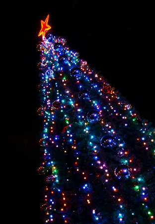 Christmas tree decorated with colorful bright lights cropped diagonally photo