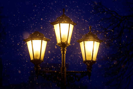 triplex: Triple lantern on a dark blue night sky and falling snow Stock Photo