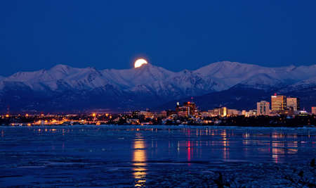 anchorage: The moon rises from behind the Chugach Mountains over Anchorage, Alaska