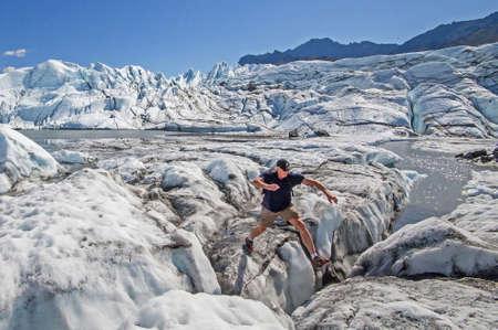 crevasse: A man jumps across a crevasse at Matanuska Glacier