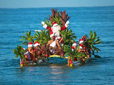 outrigger: Maui, Hawaii, USA - December 24, 2015: Santa Claus arrives by outrigger canoe at Wailea Beach at the Grand Wailea