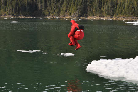 lifesaving: Person jumping from an iceberg into the water in a survival suit for training Stock Photo
