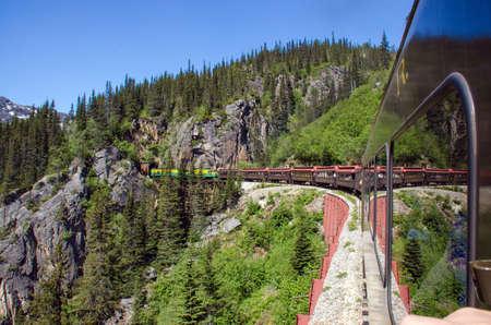 narrow gauge railroads: White Pass  Yukon Route Railroad heads into Tunnel Mountain Stock Photo