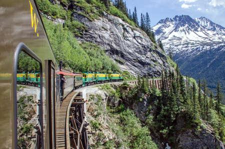 scenic: White Pass  Yukon Route Railroad travels along the cliffs heading towards Skagway, Alaska