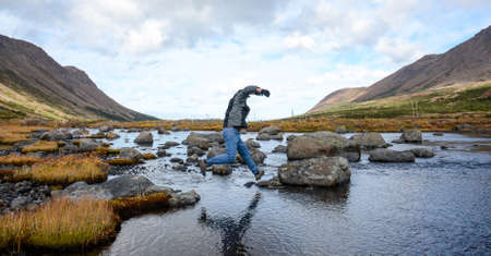 rock creek: Man crosses creek by jumping form rock to rock