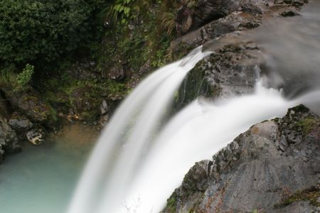 water cascades over the edge of a waterfall