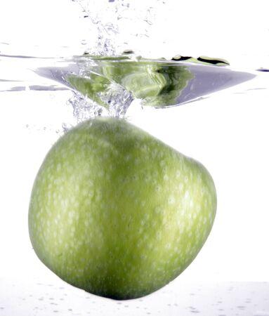 Full green apple splashing into water