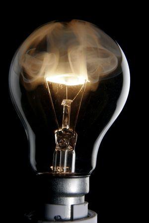 Exploding lightbulb on black background Stock Photo