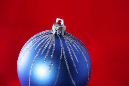 Blue christmas ball isolated on red background