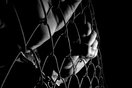 handcuffed: Hand bedrijf draads afrastering in handboeien Stockfoto
