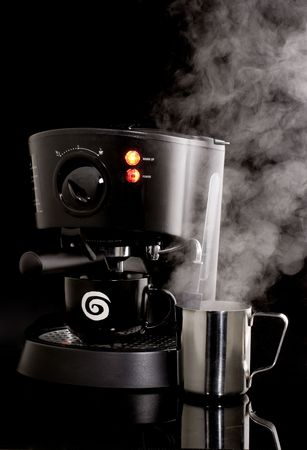 steel  milk: Espresso machine in use with frothing cup and steam against black background