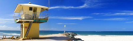 Lifeguard tower on the beach in the sun, blue sky, panoramic.