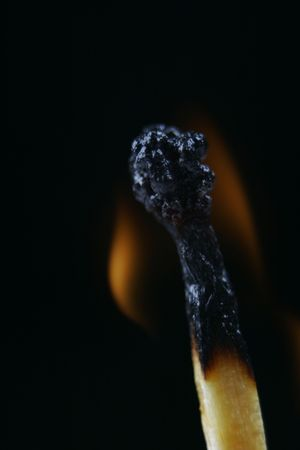 Match head on fire against black background