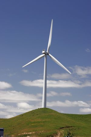 Wind turbine on top of green hill