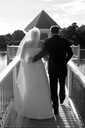 Bride and groom walking down a gazebo on a lake