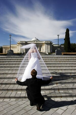 Groom holding brides veil while kneeling from behind