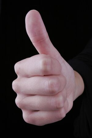 Thumbs up against black background